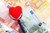 Cost of health care: stethoscope red heart on euro money — Stock Photo