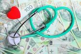 Cost of health care: stethoscope red heart polish money — Stock Photo