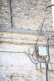 Electric controller box and tangle of cables on brick wall — Stock Photo