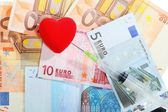 Cost of health care: red heart syringe on euro money — Stock Photo