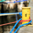 Old yellow bollard with rope in marina — Stock Photo