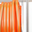 Stock Photo: Rolled up of orange plastic hose