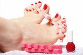 Nohou pedikúra uplatnění červené nehty na bílém pozadí — Stock fotografie