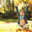 Stock Photo: Young womrelaxing playing with leaves in autumn park