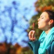 Woman having fun blowing bubbles in autumnal park — Zdjęcie stockowe #33464557