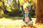 Young woman relaxing playing with leaves in autumn park — Stock Photo