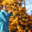 Woman having fun blowing bubbles in autumnal park — Stock fotografie