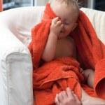 Adorable happy baby boy in orange towel — Stock Photo #33541467