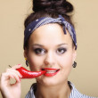 Beautiful seductive woman red lips and chilli pepper — Stock Photo