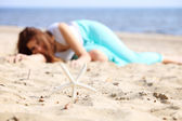 Young woman on seacoast with shell on sand — Stock Photo