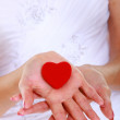 Female hands of bride with heart shaped red box — Stock Photo #33671817