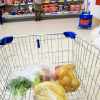 Shopping cart with grocery at supermarket — Stock Photo #33671857