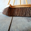 Large brooms on wooden floor housework — Stock Photo