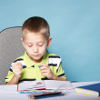 Young cute boy draws with color pencils — Stock Photo #33735617
