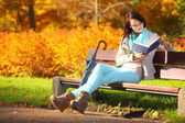 Young girl relaxing in autumnal park reading book — Stock Photo