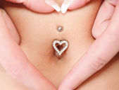 Hands heart symbol around navel piercing — Stock Photo