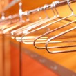 Stock Photo: Empty metal clothes hangers in row indoor