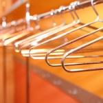 Empty metal clothes hangers in row indoor — Stock Photo #33932049