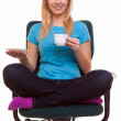 Beautiful girl relaxing in chair holds a cup of tea or coffee. — Stock Photo #34512033