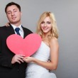 Portrait of happy bride and groom with red heart on gray — Stock Photo