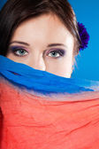 Woman hides her face with shawl on blue — Stock Photo