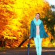 Young girl walking with umbrella in autumnal park — Stock Photo