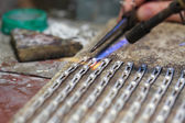 Hands of jeweller at work silver soldering — Stock Photo
