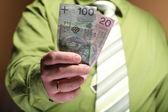 Businessman holding money 100 polish zloty — Stock Photo