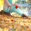 Stock Photo: Girl relaxing in the autumn park enjoying hot drink