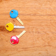House keys with colorful plastic coats caps on table — Stock Photo