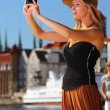 Stylish traveler woman with camera old town Gdansk — Stock Photo #35459511