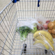 Shopping cart with grocery at supermarket — Stok fotoğraf