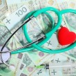 Cost of health care: stethoscope red heart polish money — Stockfoto