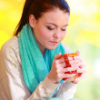 Happy girl relaxing in the autumn park enjoying hot drink — Stock Photo