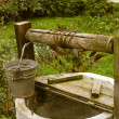 Stock Photo: Old rotten water well, rural scenery