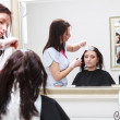 Stock Photo: Hairdresser applying color female customer at salon, doing hair dye