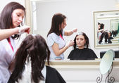 Hairdresser applying color female customer at salon, doing hair dye — Stock Photo