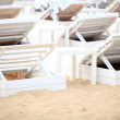 White pool chairs on sand beach — Foto Stock