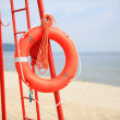 Lifeguard beach rescue equipment orange lifebuoy — Stock Photo #35884667