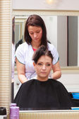 Woman dying hair in hairdressing beauty salon. By hairstylist. — Stock Photo