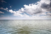 Cloudy blue sky above a surface of the sea — Stock Photo