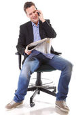 Man reads newspaper phoning - economy news — Stock Photo