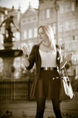 Traveler young woman with smart phone old town Gdansk — Stock Photo