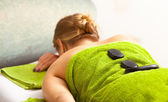 Spa salon. Woman relaxing having hot stone massage. Bodycare. — Stock Photo
