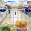 Shopping cart with grocery at supermarket — Stock Photo #36237195