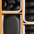 Black spa zen massage stones in wooden case as background — Foto Stock