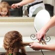 Hairdresser straightening hair little girl child in hairdressing beauty salon — Stock Photo