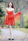 Full length fashionable woman in vibrant red dress in park — Stockfoto
