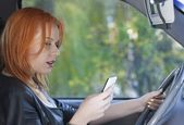 Woman driver sending text reading message on phone while driving — Stock Photo