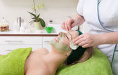 Beauty salon. Cosmetician removing facial mask from woman face. — Stock Photo